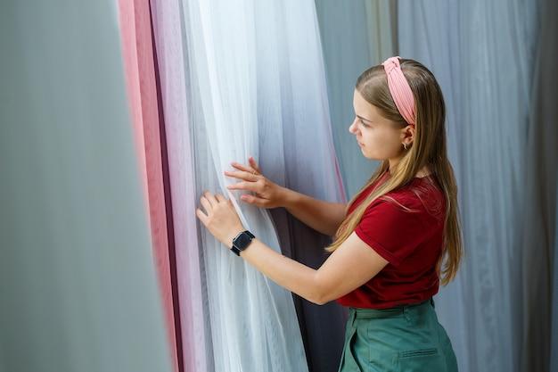 Jeune femme choisissant un tissu pour de nouveaux rideaux dans un magasin. des échantillons du rideau sont suspendus à des cintres sur un rail dans le magasin. échantillons de textures de tissu, de tulle et de rembourrage de meubles.