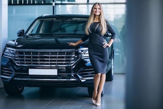 Jeune femme choisissant une voiture dans une salle d'exposition