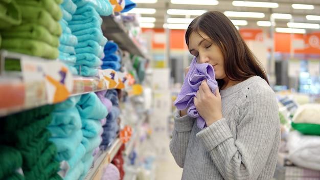 Jeune femme choisit une serviette dans un magasin de produits pour la maison.