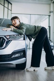 Jeune femme choosimng une voiture dans une salle d'exposition de voiture