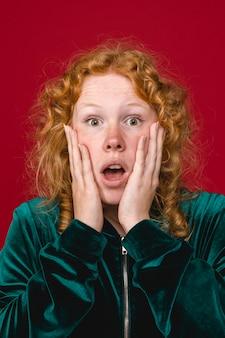 Jeune femme choquée au gingembre tenant des joues