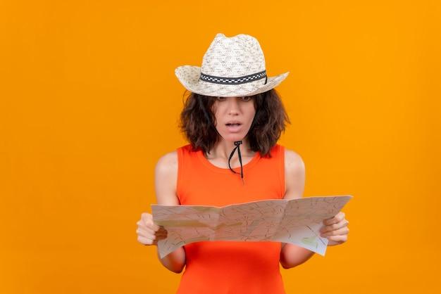 Une jeune femme choquée aux cheveux courts dans une chemise orange portant un chapeau de soleil à la carte