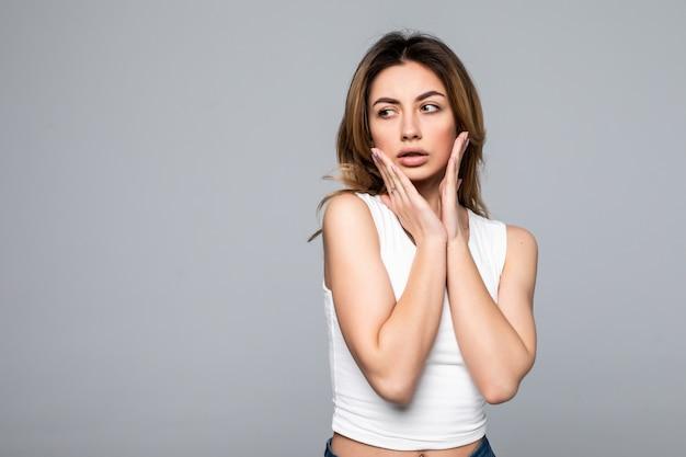 Jeune femme choquée à cause de la mauvaise nouvelle, isolée sur un mur gris