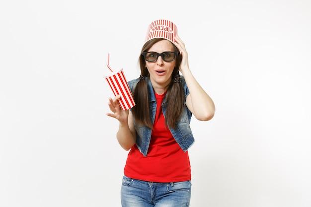 Jeune femme choquée dans des lunettes 3d avec seau pour pop-corn sur la tête en regardant un film, tenant une tasse en plastique de soda ou de cola, accrochée à la tête isolée sur fond blanc. émotions dans le concept de cinéma.