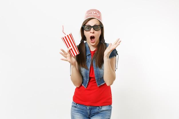 Jeune femme choquée dans des lunettes 3d avec seau pour pop-corn sur la tête en regardant un film, tenant une tasse en plastique de soda ou de cola, écartant les mains isolées sur fond blanc. émotions dans le concept de cinéma.