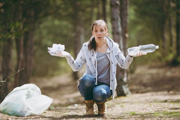 Jeune femme choquée dans des vêtements décontractés nettoyant et écartant les mains avec des ordures dans le parc sur un mur vert