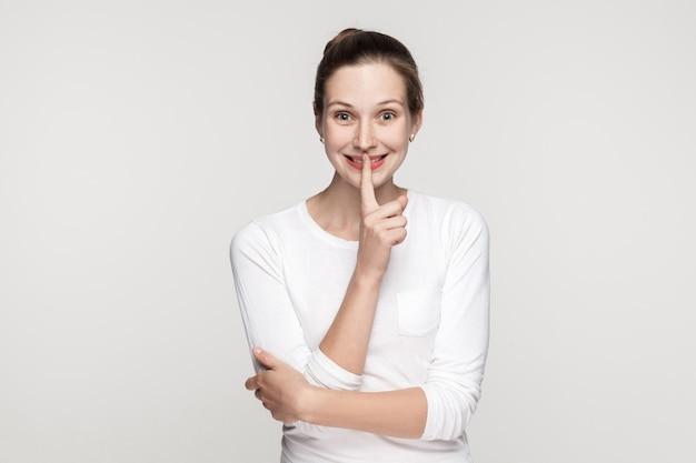 Jeune femme choquée, montrant chut chanter et regardant avec de grands yeux la caméra et souriant. studio shot, isolé sur fond gris