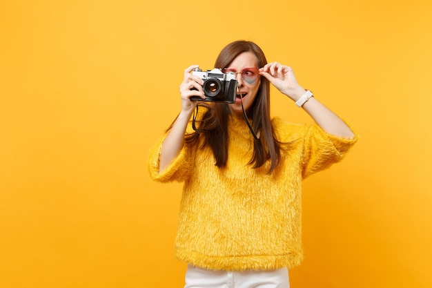 Jeune femme choquée et perplexe tenant des lunettes cardiaques et prenant des photos sur un appareil photo vintage rétro isolé sur fond jaune vif. les gens émotions sincères, concept de style de vie. espace publicitaire.