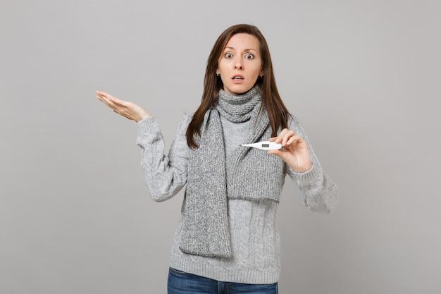 Jeune femme choquée en pull gris, écharpe écartant les mains tenant un thermomètre isolé sur fond de mur gris. mode de vie sain, traitement des maladies malades, concept de saison froide. maquette de l'espace de copie.