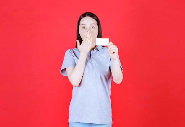 Jeune femme choquée tenant une carte de visite et portant la main à sa bouche