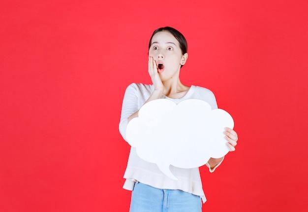 Jeune femme choquée tenant le conseil d'idée et regardant loin la bouche ouverte