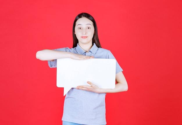 Jeune femme choquée tenant une planche et regardant à l'avant