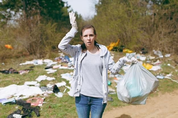 Jeune femme choquée en vêtements décontractés, nettoyage de gants tenant des sacs poubelles et écartant les mains dans un parc jonché