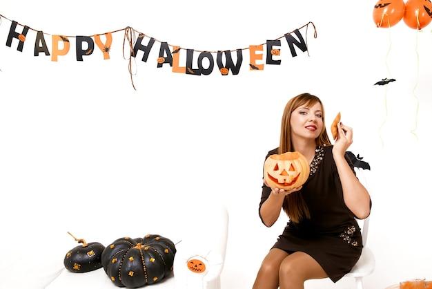 Jeune femme à la citrouille noire en décoration d'halloween