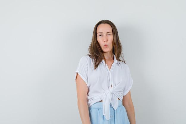 Jeune femme clignant des yeux et posant à l'avant en chemisier blanc et jupe bleu clair et à la charmante