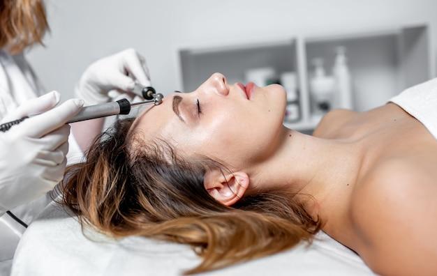 Jeune femme à la clinique de spa recevant un traitement stimulant du visage