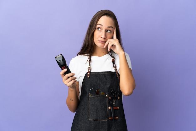 Jeune femme de coiffeur sur fond isolé pensant une idée