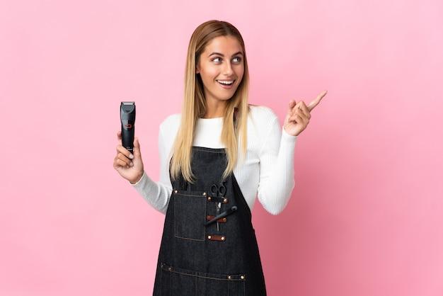 Jeune femme de coiffeur isolée sur un mur rose dans l'intention de réaliser la solution tout en soulevant un doigt