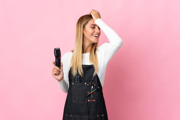 Jeune femme de coiffeur isolée sur un mur rose a réalisé quelque chose et l'intention de la solution