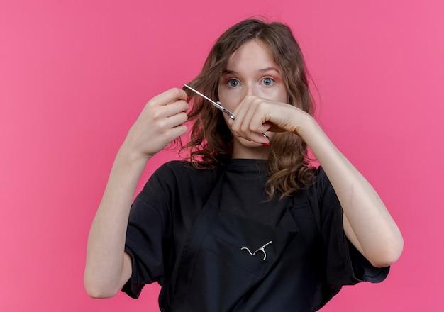 Jeune femme, coiffeur, porter, uniforme, couper, cheveux, à, ciseaux, regarder front