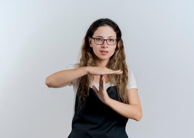 Jeune femme de coiffeur professionnel en tablier à l'avant faisant le geste de temps avec les mains debout sur un mur blanc