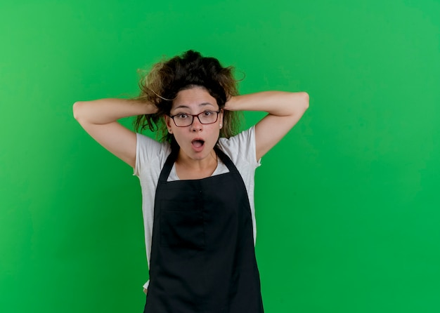 Jeune femme de coiffeur professionnel en tablier à l'avant en tirant ses cheveux dans la panique debout sur le mur vert