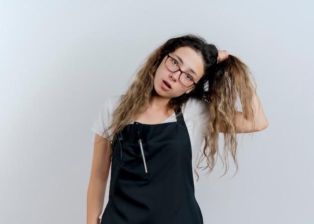 Jeune femme de coiffeur professionnel en tablier confus toucher ses cheveux