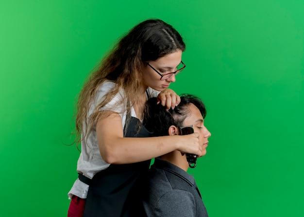 Jeune femme de coiffeur professionnel en tablier coupe cheveux avec tondeuse de client homme