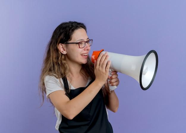 Jeune femme de coiffeur professionnel en tablier parlant au mégaphone souriant joyeusement