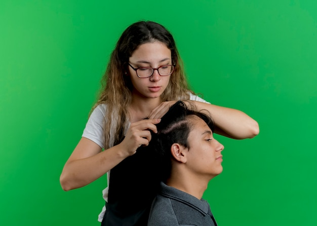 Jeune femme de coiffeur professionnel en tablier peignant les cheveux du client homme debout sur le mur vert