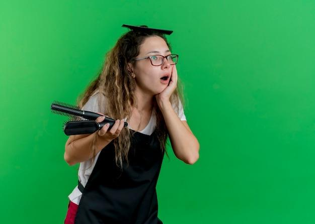 Jeune femme de coiffeur professionnel en tablier tenant des brosses à cheveux à côté d'être surpris debout sur le mur vert