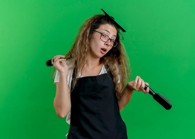 Jeune femme de coiffeur professionnel en tablier tenant des brosses à cheveux avec sourire sur le visage