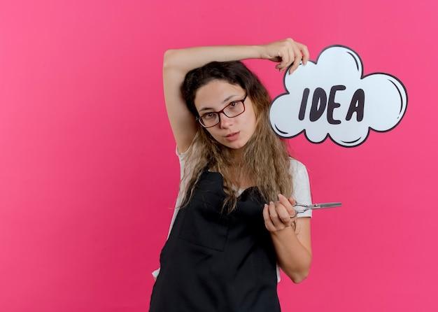 Jeune femme de coiffeur professionnel en tablier tenant des ciseaux et signe de bulle de discours avec idée de mot souriant confiant