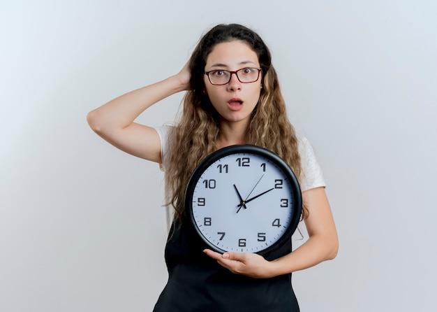 Jeune femme de coiffeur professionnel en tablier tenant horloge murale regardant à l'avant confus debout sur un mur blanc