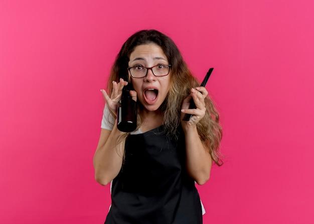 Jeune femme de coiffeur professionnel en tablier tenant un peigne et un spray en criant de panique