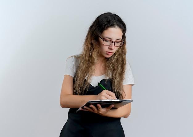 Jeune femme de coiffeur professionnel en tablier tenant le presse-papiers et un stylo écrit quelque chose avec un visage sérieux debout sur un mur blanc