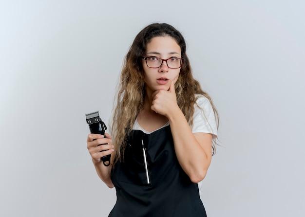 Jeune femme de coiffeur professionnel en tablier tenant tondeuse à l'avant avec la main sur le menton pensant debout sur un mur blanc