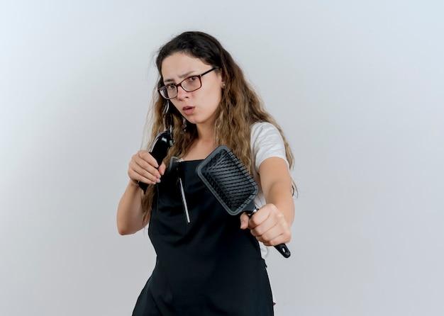Jeune femme de coiffeur professionnel en tablier tenant une tondeuse et une brosse à cheveux à l'avant d'être inquiet debout sur un mur blanc