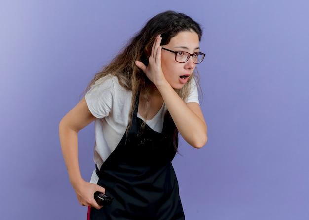 Jeune femme de coiffeur professionnel en tablier tenant tondeuse à côté avec la main près de l'oreille en essayant d'écouter debout sur le mur bleu
