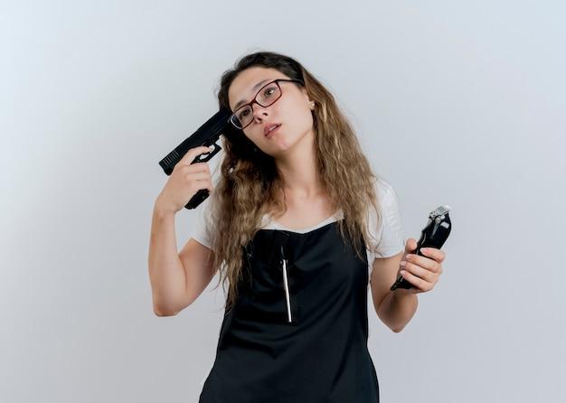 Jeune femme de coiffeur professionnel en tablier tenant tondeuse et pistolet près de son temple à côté fatigué et ennuyé debout sur un mur blanc