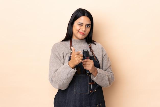 Jeune femme coiffeuse colombienne isolée sur le mur beige pointe le doigt vers vous