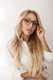 Jeune femme avec une coiffure blonde dans des verres élégants dans une chemise blanche près d'un mur gris