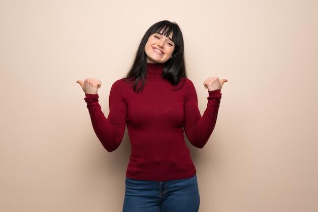 Jeune femme, à, col roulé rouge, donner, a, pouces haut, geste, à, deux, mains, et, sourire