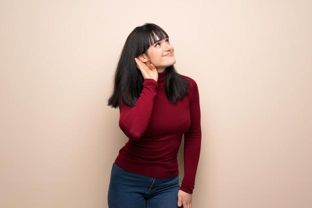 Jeune femme avec un col roulé rouge écoutant quelque chose en mettant la main sur l'oreille