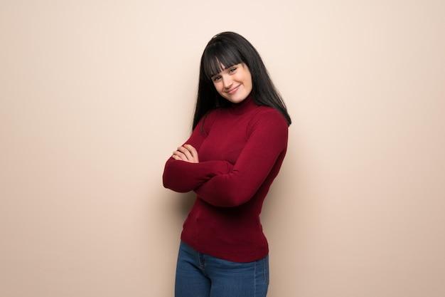 Jeune femme avec un col roulé rouge, gardant les bras croisés en position latérale tout en souriant