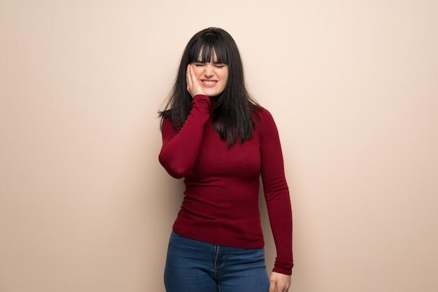 Jeune femme avec col roulé rouge avec mal aux dents