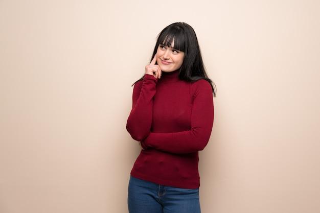 Jeune femme avec un col roulé rouge, pensant à une idée tout en levant les yeux