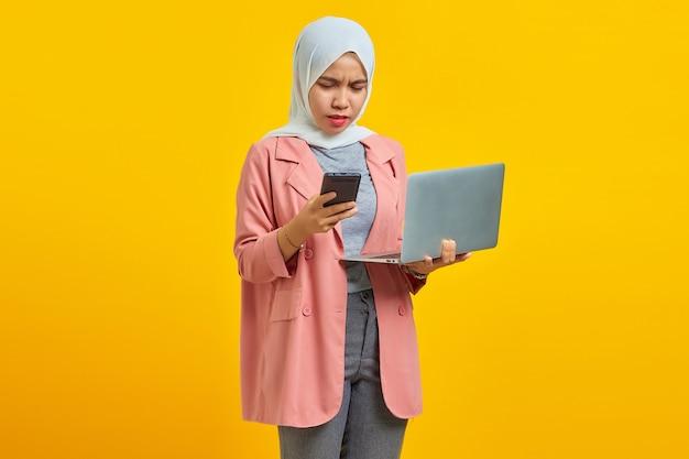 Jeune femme en colère à l'aide d'un ordinateur portable et d'un téléphone portable en se tenant isolé sur fond jaune