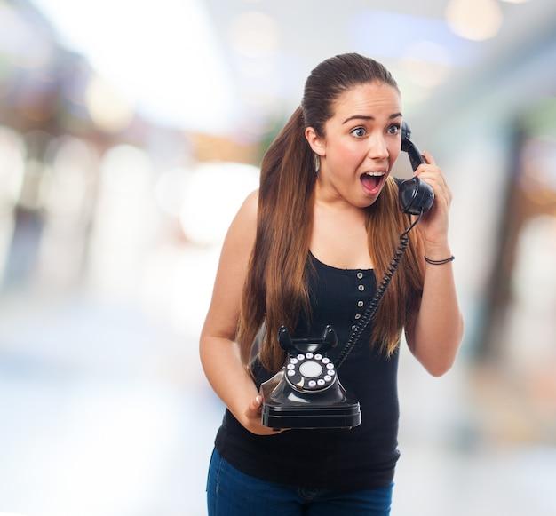 Jeune femme en colère à l'aide d'un téléphone vintage