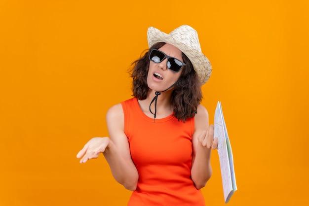 Une jeune femme en colère aux cheveux courts dans une chemise orange portant un chapeau et des lunettes de soleil tenant les mains d'ouverture de la carte